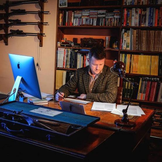 Diggory Hadoke, Vintage Guns Journal Editor sitting at his desk working hard